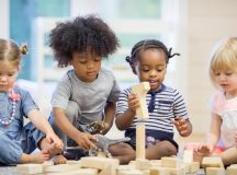 A multi-ethnic group of toddlers are sitting together on the floor holding playing with wood blocks together.